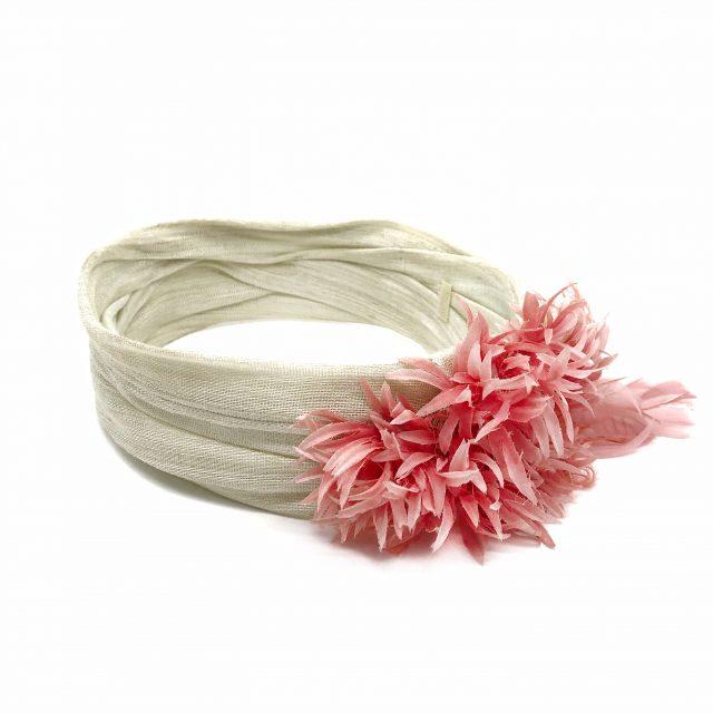 El Turbante Beige con Flor y Plumas Rosasde Lito & Lola está creado a mano de nuestras expertas en tocados y accesorios para el pelo.